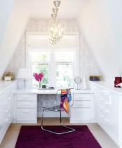 a glam attic home office with two storage units and a built-in desk, an accent wall done with printed wallpaper, chic glam chandeliers, an accent purple rug and a sheer chair