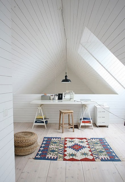 a clean white attic home office with planked walls and a ceiling, two windows, a trestle desk, a stool and a printed rug for a bold touch