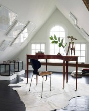 an elegant attic home office with white windows, gallery walls, a stained vintage desk, a wooden chair and some glass storage units