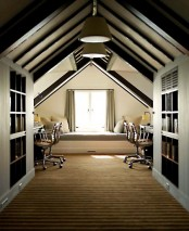 a cool shared attic home office with dark wooden beams on the ceiling, desks and leather chairs, a daybed at the window and large bookcases for storage