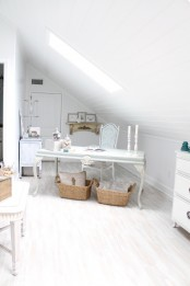a white attic home office with a skylight, a refined desk and a vintahe chair, beautiful storage units, baskets and a small gallery wall on a shelf