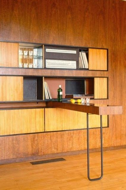 a yellow plywood wall unit with closed storage compartments and a bar countertop on a hairpin leg
