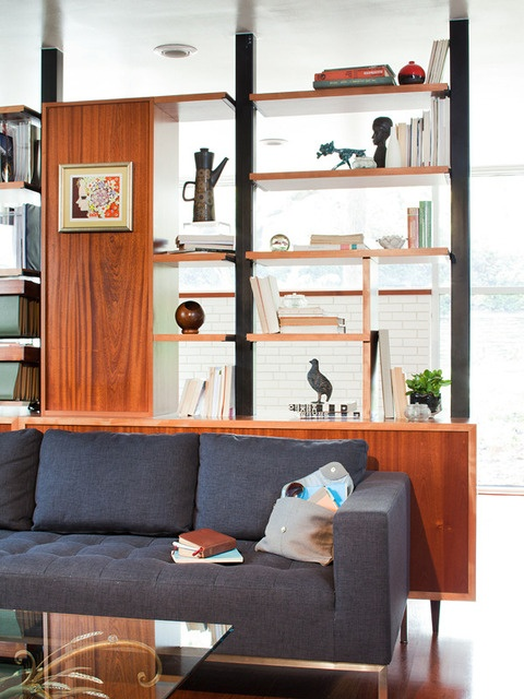 a large storage unit that acts as a space divider, open shelves and storage compartments is a very functional idea