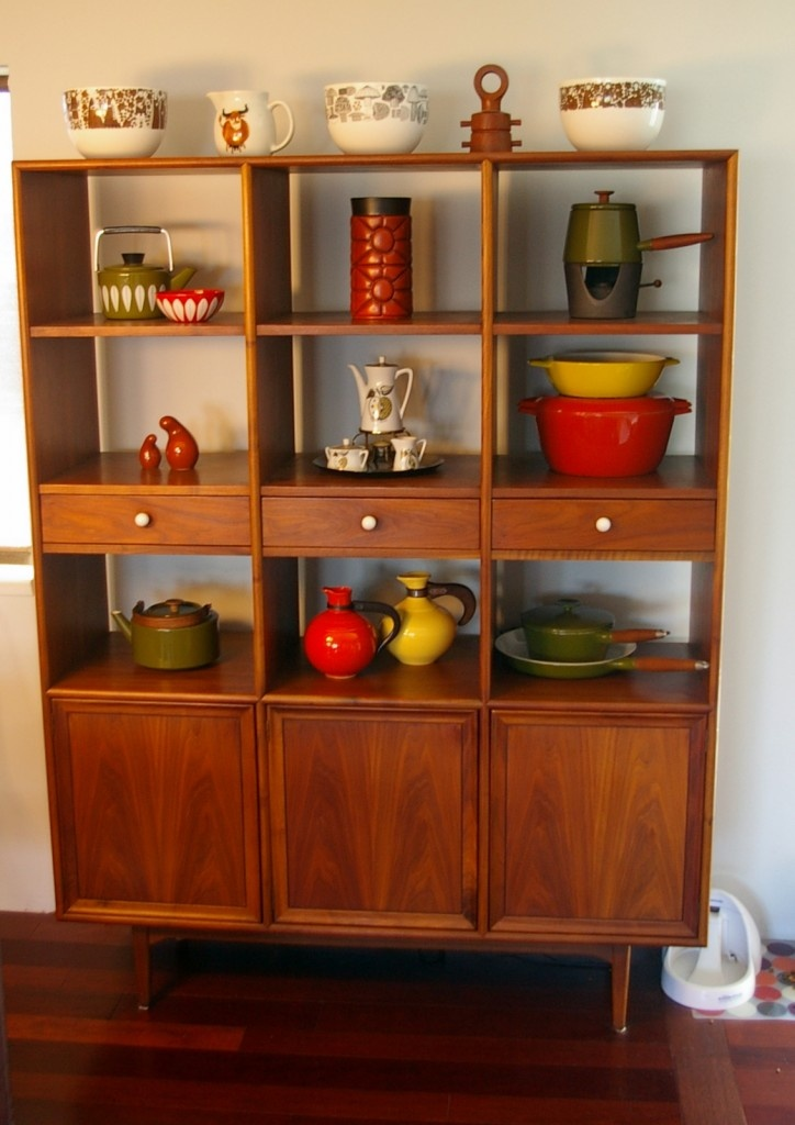 a rich stained storage unit with closed compartments, drawers and open shelves is a timeless piece to use