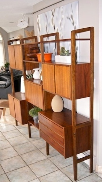 a large storage unit featuring cabinets and open shelves is a stylish idea for a mid century modern interior