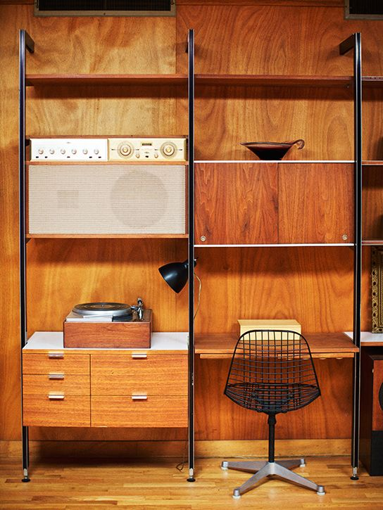 a large rich-stained wall unit with closed storage compartments, drawers and open shelves plus a mini desk integrated