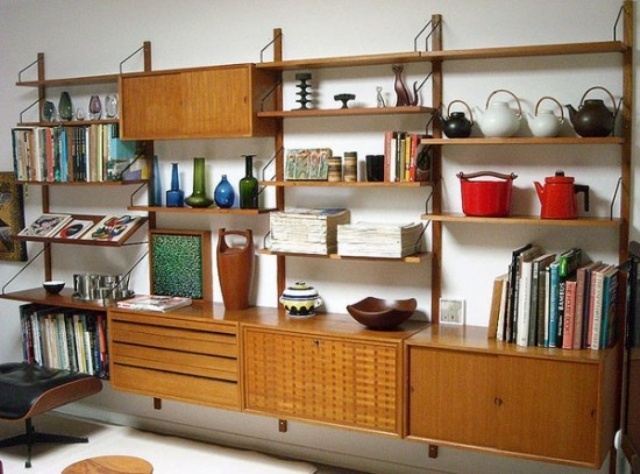 a large wall mounted storage unit with cabinets, drawers and shelves including slanted ones, all placed symmetrically