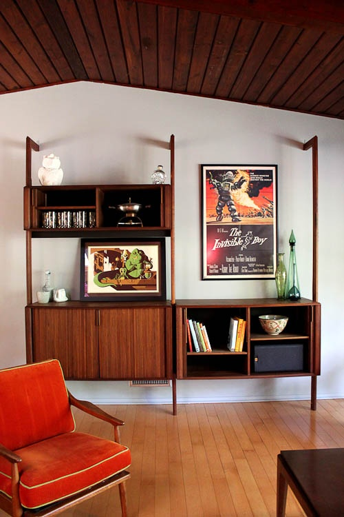 a mid-century modern wooden wall unit with open and closed compartments and artworks