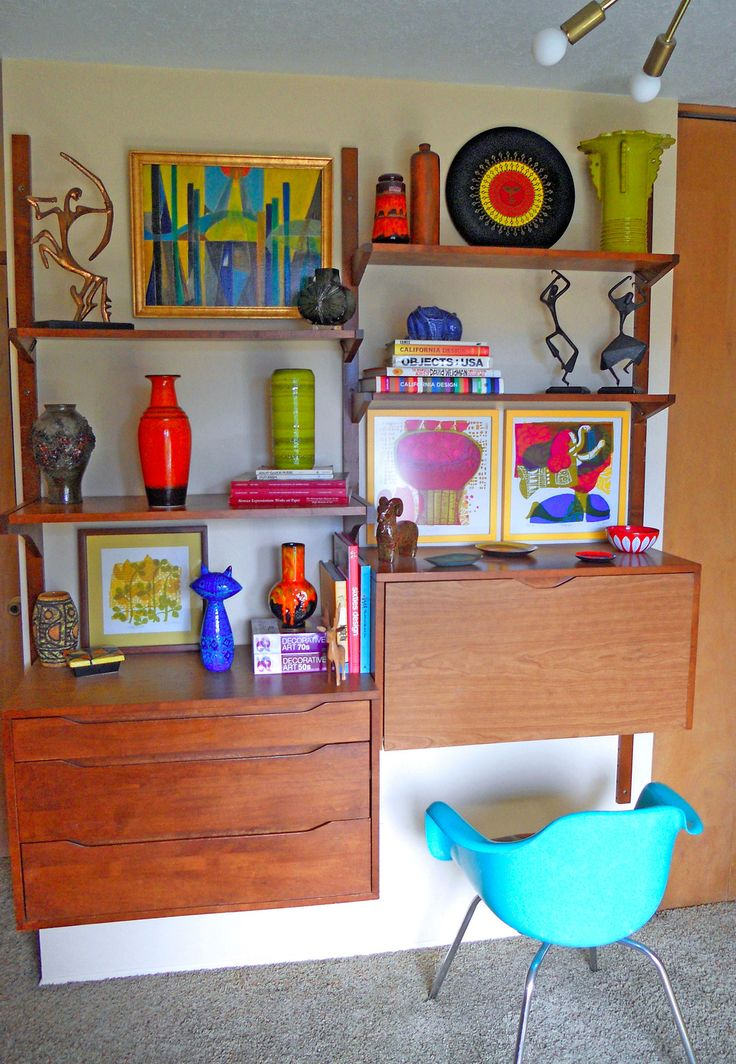 a rich stained mid century modern wall unit with open shelves, a closed compartment and a bureau that features a desk