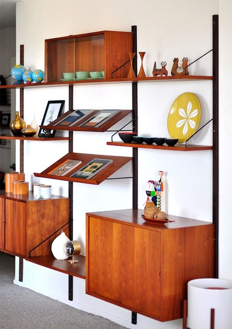 a mid-century modern wall unit with open shelves, cabinets and slanted shelves of a rich stain color