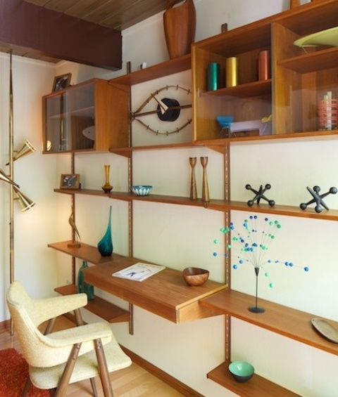 an oversized wooden wall unit with shelves, open box shelves, drawers and a mini floating desk integrated