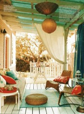 a boho porch with white wooden and woven furniture, orange and turquoise textiles, a jute ottoman and Moroccan lamps