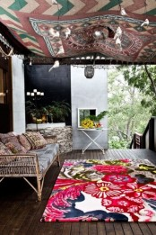 a tropical boho porch with a rattan daybed and a table, super colorful textiles and a blanket over the space plus greenery