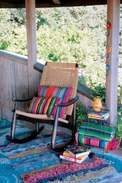 a colorful boho porch with bright printed textiles, a woven chair and colorful books stacked