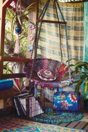 a bright gypsy porch with colorful curtains hanging, a woven hanging chair, colorful textiles and a bright rugs