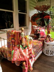 a boho porch with a sleeping nook – metal furniture with colorful printed textiles, bright umbrellas and a white table with toys