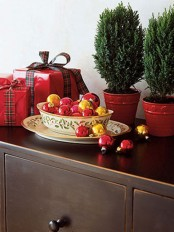 a bowl with gold and red Christmas ornaments is a cool decoration or centerpiece for winter holidays