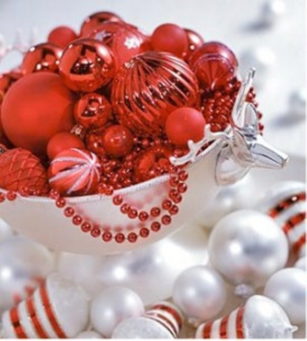 a silver bowl with red ornaments of various sizes and white ornaments around is a cool idea for festive table decor