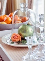 a chic glass cloche with a large green Christmas ornament and a bloom is an elegant holiday centerpiece