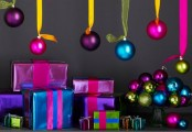 colorful Christmas ornaments hanging over the space and in a bowl are amazing for holiday spaces
