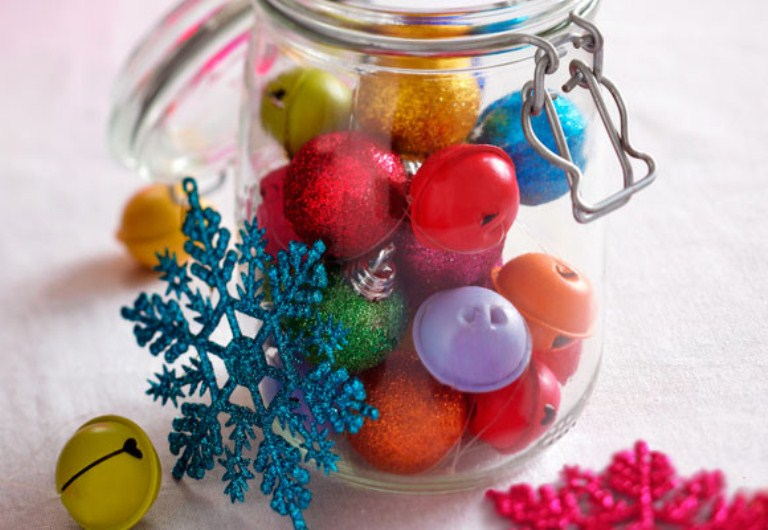 a jar with mini colorful Christmas ornaments and bells plus colorful snowflakes for festive decor