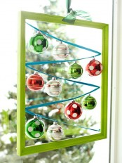 a green frame with colorful Christmas ornaments hanging inside is a cool and creative Christmas decorations