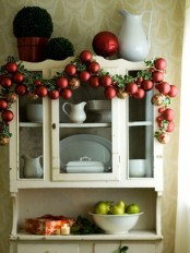 a holiday garland of colorful ornaments and foliage is a cool decoration for Christmas spaces – from kitchens to living rooms