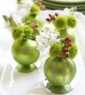 colorful Christmas ornaments used as mini vases for blooms and berries is a cool idea for any holiday table