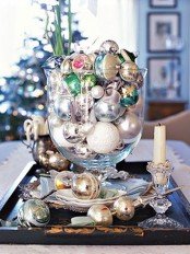 a tray and a glass bowl all filled with various colorful Christmas ornaments and candles for decor