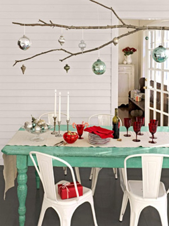 a branch with some Christmas ornaments hanging down is a cool overhead decoration for a holiday or festive space