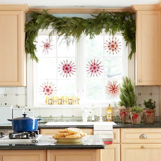 Hang decorative snowflakes in red tones and add an evergreen swag on top of the window.
