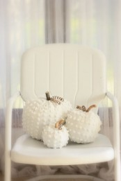 white fabric pumpkins with wooden stems and twine are chic and ethereal and will bring a cozy feel to the space