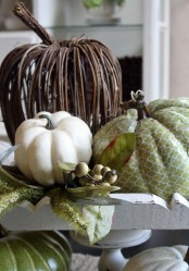 an arrangement of a vine, faux and green fabric pumpkin, greenery and berries is a stylish rustic fall centerpiece