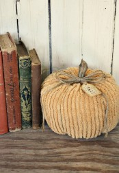 a muted color fabric pumpkin with wooden stems and twine is a stylish shabby chic decoration for the fall