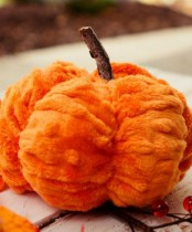 a bright orange faux fur pumpkin with a stem is a gorgeous decoration for the fall