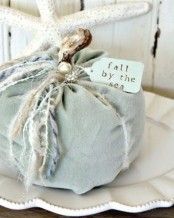 a light blue fabric pumpkin with various twine and yarn, with beads and pearls for coastal fall decor