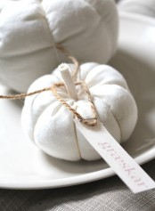 a white fabric pumpkin with twine and a tag can be used as decor, a favor or escort card in the fall