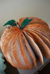 a newspaper pumpkin with orange edges, a stem and green felt leaves is an easy DIY to make and can be made very fast