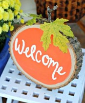 a wood slice in orange, with a stem and a real leaf is a lovely fall decoration with a strong rustic touch
