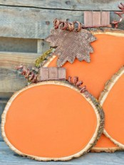 an arrangement of orange wood slices, twine and plywood leaves is a cool idea for indoor or outdoor decor