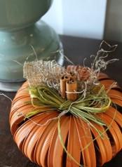 an orange pumpkin made of tin rings, hay, burlap, twine and cinnamon sticks is a stylish idea