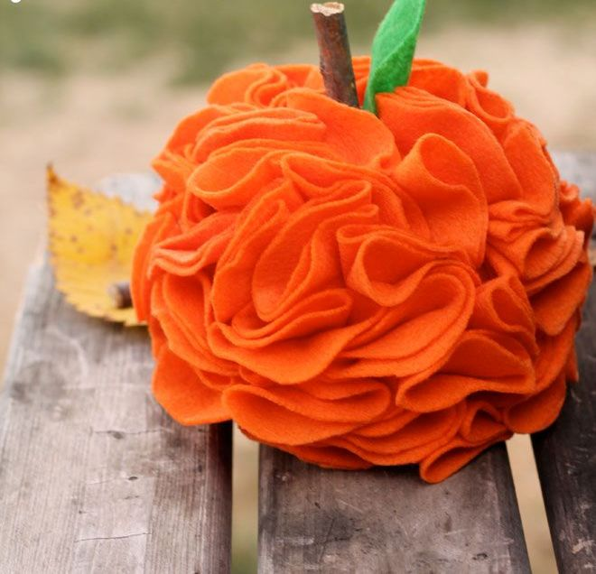a bright orange fabric ruffle pumpkin with a wooden stem and a leaf is a fun idea for fall decor and you can DIY it