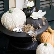 a black urn with a newspaper decoupage pumpkin, black pumpkins, hay, newspaper and fabric leaves