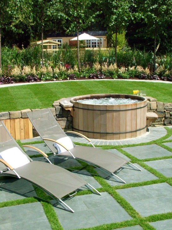 Wooden hot tub that connects two lawn levels and looks like it is built-in.