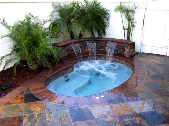Combining a jaccuzzi with a backyard waterfall is definitely a cool way to go.