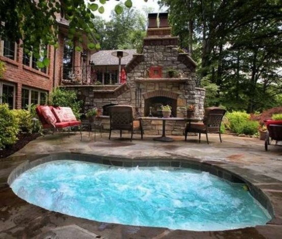 A patio with an in-ground hot tub jacuzzi and a fireplace could make every summer evening special.
