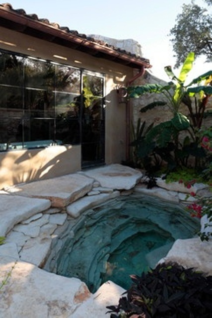 Natural stone garden tub design. Looks like it's a located in some cave.