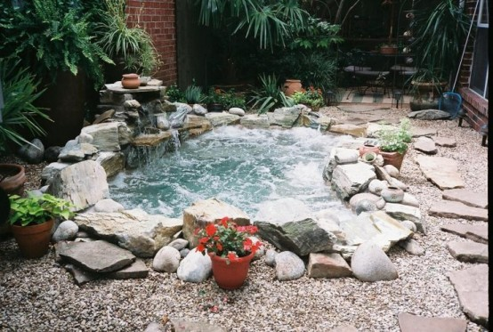 Beautiful in-ground natural-looking stone hot tub  surrounded by pebbles.