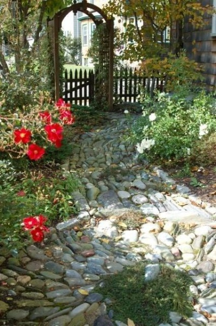 a stone garden path of muted color stones forming a chaotical pattern will fit a secret garden or a fairy-inspired one