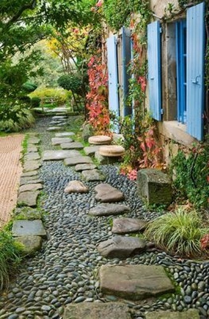 a black and grey gravel path with large rough stones on top that add eye-catchiness and a bold touch to the space